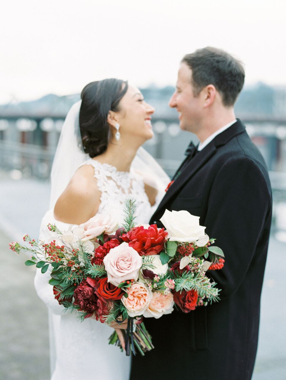 Bride and groom smiling with floral bouquet